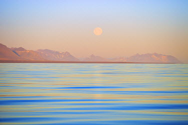 EU21DSL0032 Arctic, Svalbard, Longsfjorden. Moonrise rises above dust at midnight. Pastel shades are created by atmospheric dust and aerosol pollution which ultimately melts the glaciers.