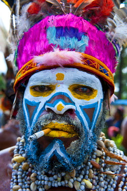 OC12MRU0162 Colorful dress and face painted local tribesman celebrating the traditional Sing Sing in in the Highlands of Papua New Guinea, Melanesia