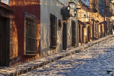 SA13BTH0006 Mexico, San Miguel de Allende. Sunlight streams down a cobblestone lane in the village.