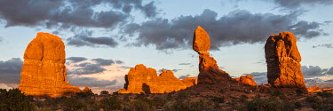 US45JZI0295 USA, Utah, Arches National Park. Balanced Rock with clouds at sunset