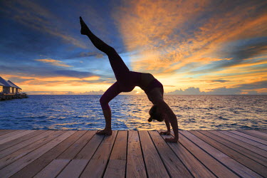 MD01352 Maldives, South Ari Atoll, Thudufushi Island, Diamonds Thudufushi Resort, woman practising Yoga at sunset (MR)