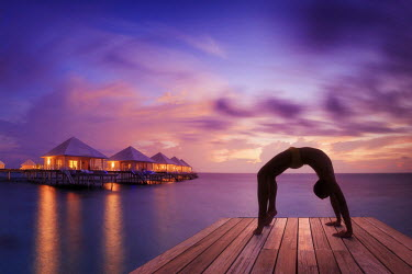 MD01373 Maldives, South Ari Atoll, Thudufushi Island, Diamonds Thudufushi Resort, man practising Yoga at sunset (MR)
