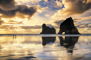 NZ9043AW Couple Walking on Wharariki Beach at Sunset, New Zealand