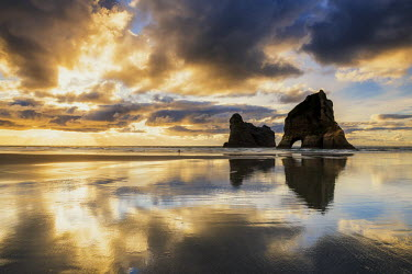 NZ9044AW Lone Person on Wharariki Beach at Sunset, New Zealand