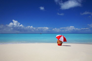 ANB0008AW Woman Sitting on Beach with Red & White Umbrella, Barbuda, Caribbean, West Indies