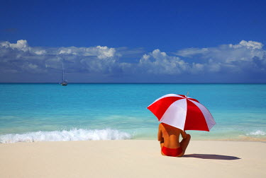 ANB0009AW Woman Sitting on Beach with Red & White Umbrella, Barbuda, Caribbean, West Indies