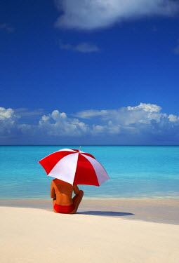 ANB0010AW Woman Sitting on Beach with Red & White Umbrella, Barbuda, Caribbean, West Indies