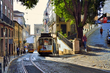 POR9089AW A tramway in Alfama district with the Motherchurch (Se Catedral) in the background. Lisbon, Portugal