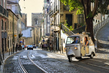 POR9091AW A tuk tuk in Alfama district with the Motherchurch (Se Catedral) in the background. Lisbon, Portugal
