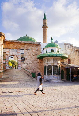 ISR0157 Israel, Akko. Muslim woman walking in front of the entrance to the El Jezzar Pasha Mosque with the green domed sabil on the side. Unesco.