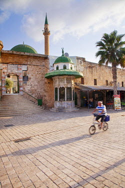 ISR0158 Israel, Akko. Man on a bike cycling in front of the entrance to the El Jezzar Mosque. Unesco.