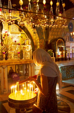 ISR0169 Israel, Jerusalem. Believer lighting a candle at the Chapel of Calvary. Unesco.