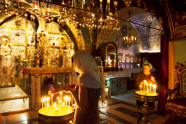 ISR0170 Israel, Jerusalem. Believers lighting a candle at the Chapel of Calvary. Unesco.