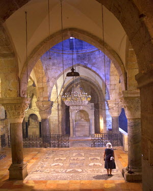 ISR0180 Israel, Jerusalem. Woman standing at the crypt in front of the Chapel of St Helena also known as St Gregory the Illuminator at the Church of the Holy Sepulchre reminiscent of a litograph by David Robe...