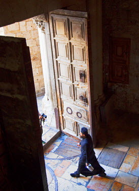 ISR0181 Israel, Jerusalem. A Greek Orhtodox Monk walking out of the Church of the Holy Sepulchre. Unesco.