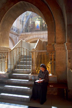 ISR0213 Israel, Jerusalem. Woman reading through a religious book at the Chapel of Calvary at the Church of the Holy Sepulchre. Unesco.