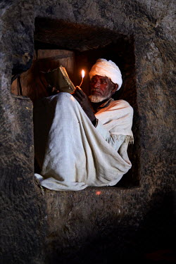 ETH3080AW Priest reads his bible in the light of a candle while sitting in a nook, Ethiopia, Africa