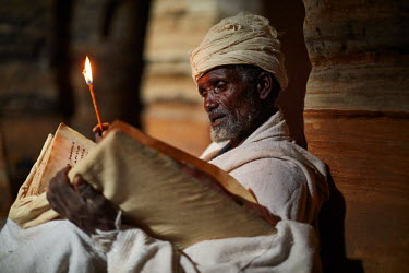 ETH3091AW Priest reads his bible in the light from the door of the church, Ethiopia, Africa