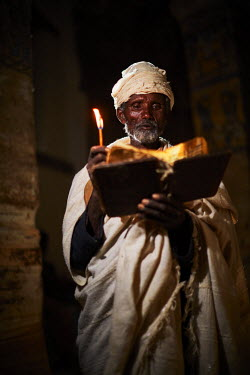ETH3092AW Priest reads his bible in the light from the door of the church, Ethiopia, Africa