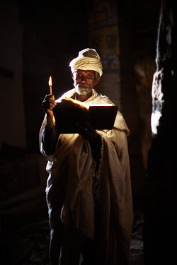 ETH3094AW Priest reads his bible in the light from the door of the church, Ethiopia, Africa