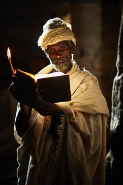 ETH3095AW Priest reads his bible in the light from the door of the church, Ethiopia, Africa