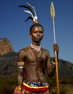 KEN10291AW Samburu warrior standing in front Mt Poi, Kenya, Africa