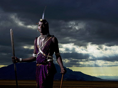 TZ3406AW Maasai warrior standing at dusk on the slat flats of lake Natron  with Shompole mountain in the background, Tanzania, Africa