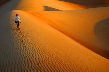 HMS2102967 United Arab Emirates, Abu Dhabi, Liwa Oasis, Moreeb Hill, Tal Mireb, woman in the sand dunes of the Rub Al Khali desert (Empty Quarter)