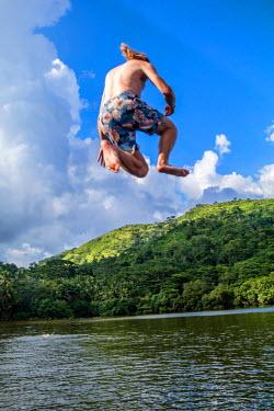 TTB0067AW Monnos Island, Trinidad and Tobago,  West Indies,  Man jumps into the Carrabbean Sea.