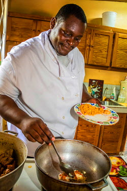TTB0105AW Port of Spain, Trinidad and Tobago,  West Indies, Afro-Creole Cheff in his Home kitchen kitchen stir frying vegetables while preparing lunch.