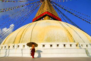 HMS0208211 Nepal, Kathmandu Valley listed as World Heritage by UNESCO, Kathmandu, Bouddhanath Stupa, Tibetan pilgrim with umbrella, monk