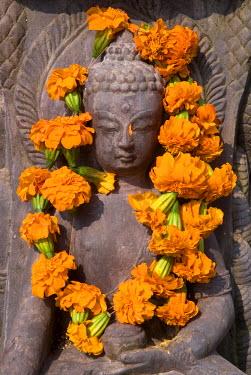 HMS0208220 Nepal, Kathmandu Valley listed as World Heritage by UNESCO, Kathmandu, Swoyambhunath Stupa, statue, Divinity with flowers offerings