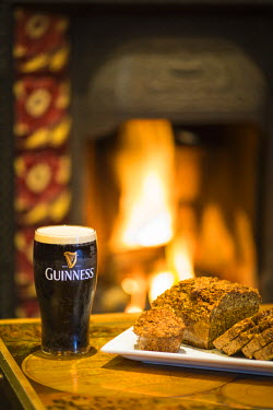 IRL0523AW Ireland, County Roscommon, Ballinlough. A pint of Guinness, Guinness Bread and a roaring fire in a traditional Irish Pub.