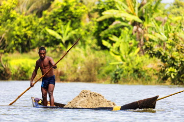 MAD1034 Africa, (easthern) Madagascar, Tamatave, Pangalanes Lakes canal system, a man transporting sand by pirogue canoe