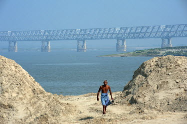 IND8228 India, Bihar, Munger (aka Munghyr). A villager framed by the massive Munger Ganga Bridge spanning the River Ganges. Opened in 2016 to rail traffic (and with roads expected to follow), it is one of Ind...