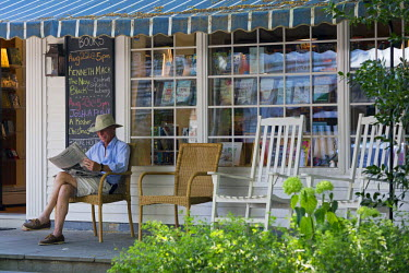 HMS1803858 United States, Massachusetts, Cape Cod, Martha's Vineyard island, Edgartown, Main Street, the independent bookstore Edgartown Books, man reading a newspaper on the front porch