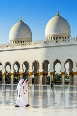 UAE0397AW Two Middle Eastern men traditionally dressed walking in the courtyard of the Sheikh Zayed Mosque, Abu Dhabi, United Arab Emirates