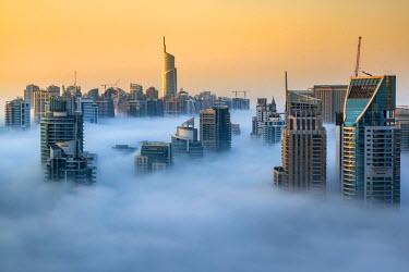 UAE0409AW Foggy sunrise with Dubai Marina's skyscrapers towering over the low clouds, Dubai, United Arab Emirates