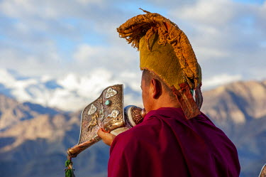 IND8267 India, Jammu & Kashmir, Ladakh, Thiksey. Each morning after sunrise monks blow conch horns, or dung-dkar, from the rooftop of Thiksey Monastery.