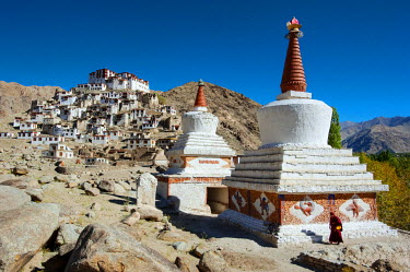 India, Jammu & Kashmir, Ladakh, Chemrey. A monk strolls around a chorten near the 17th-century Chemrey Monastery, or gompa, which stands on a hill overlooking Chemrey village.