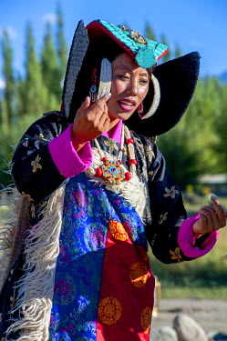 IND8282 India, Jammu & Kashmir, Ladakh. A Ladakhi woman wears traditional clothes including a turquoise-studded headdress, or perak, and a ceremonial brocade mantle or shawl.