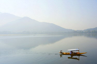 IND8301 India, Jammu & Kashmir, Kashmir, Srinagar. Tourists enjoy Srinagar's celebrated Dal Lake and its Zabarwan Hills backdrop from the comfort of a shikara - small wooden boats still widely used for transp...