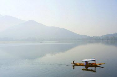 IND8301 India, Jammu & Kashmir, Kashmir, Srinagar. Tourists enjoy Srinagar's celebrated Dal Lake and its Zabarwan Hills backdrop from the comfort of a shikara - small wooden boats still widely used for transp...