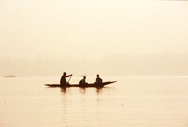 IND8310 India, Jammu & Kashmir, Kashmir, Srinagar. Kashmiri schoolboys are paddled across Srinagar's celebrated Dal Lake in a shikara - small wooden boats still widely used for transport and tourism.