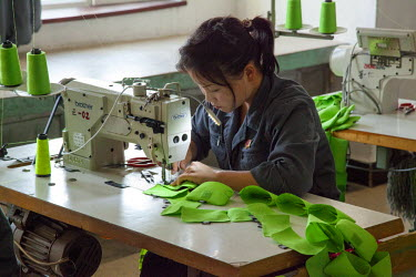 NKO0285 A young girl stitching material at a garment factory in Rason, North Korea