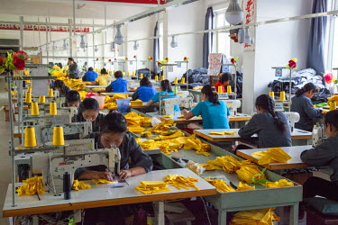 NKO0286 Girls stitching material at a garment factory in Rason, North Korea