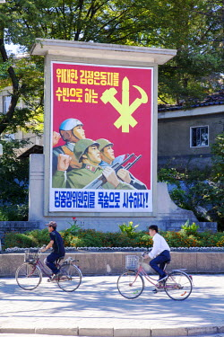 NKO0337 Two local citizens bicycling past a propaganda poster in Kaesong, North Korea