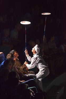 NKO0354 A juggler balancing spinning plates on poles at the Pyongyang State Circus, North Korea