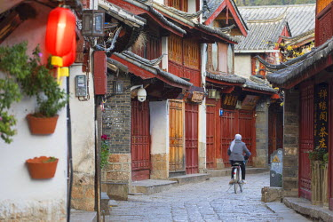 Woman cycling along alleyway, Lijiang (UNESCO World Heritage Site), Yunnan, China