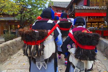 CH10911AW Naxi women wearing traditional clothing in parade, Lijiang (UNESCO World Heritage Site), Yunnan, China